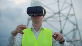 Środkowego planu męski energetyczny inżynier w rzeczywistość wirtualna szkłach i biały hełm na tle wysokonapięciowa władza zbiory wideo