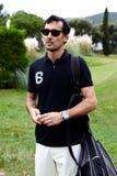 Środkowy mężczyzna w okularów przeciwsłonecznych komesie z szkolenie golfem Zdjęcie Stock