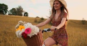 Środkowy plan jest blondynką w kapelusz przejażdżkach rower z kwiatami i uśmiechami zdjęcie wideo