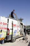 Środkowy wschód Mitzpe Ramon, Izrael Luty 29, A pracownik z drabiną na dachu samochód Zdjęcia Stock