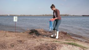 Środowiskowi rozwiązania, dziewczyna wolontariusz zbierają plastikowego grat w torbie na śmiecie i dają pozytywnemu gestowi na za zdjęcie wideo
