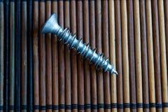 Śrubuje odosobnionego na drewnianej tło teksturze dla strony internetowej ot urządzeń przenośnych, domowy swatch Zdjęcie Royalty Free