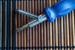Śruby i śrubokręt odizolowywający na drewnianej tło teksturze dla strony internetowej ot urządzeń przenośnych, domowy swatch Obrazy Stock
