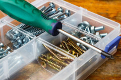 Śruby i rygle w składowym pudełku z śrubokrętem na workbench Fotografia Royalty Free