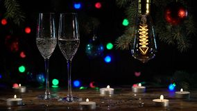 Świąteczna atmosfera dwa szkła nalewa szampana na stole jest zaświecającymi żarówkami swobodny ruch zdjęcie wideo