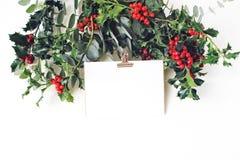 Świąteczna Bożenarodzeniowa mockup scena Kartka z pozdrowieniami z złotą papierową segregator klamerką, eukaliptusa i holly czerw fotografia stock