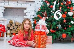 Świąteczna mała dziewczynka otwiera prezent w domu Zdjęcie Royalty Free
