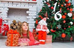 Świąteczna mała dziewczynka otwiera prezent w domu Obrazy Royalty Free