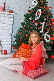 Świąteczna mała dziewczynka otwiera prezent w domu Obrazy Stock