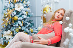 Świąteczna mała dziewczynka otwiera prezent w domu Obraz Royalty Free