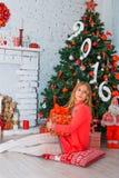 Świąteczna mała dziewczynka otwiera prezent w domu Fotografia Stock