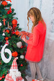 Świąteczna mała dziewczynka otwiera prezent w domu Fotografia Royalty Free