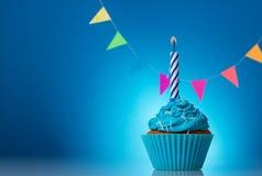 Świąteczne babeczki dla urodziny na błękitnym tle z kolorową girlandą i świeczką obrazy stock