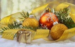 Świąteczne Bożenarodzeniowe piłki, mały pudełko z teraźniejszością, złocisty faborek i jodła, rozgałęziają się fotografia stock