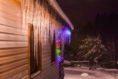 Świąteczni iluminujący sople na domu wiejskim obraz royalty free