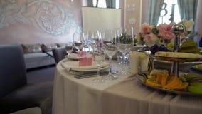 Świąteczny ślubu stołu położenie z różowymi kwiatami, pieluchy, szkła zbiory wideo