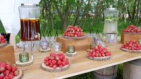 Świąteczny drewno stół z truskawkami, miotaczem od chłodno herbaty i cytryną, bezalkoholowy mojito na tło naturze, zdjęcie wideo