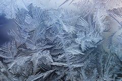 świąteczny mroźny wzór z białymi płatkami śniegu na błękitnym tle na szkle obraz stock