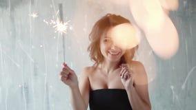 Świąteczny portret dziewczyna z sparklers w ręce uśmiechnięta dziewczyna przy przyjęciem piękni czerń sukni kobiety potomstwa zdjęcie wideo