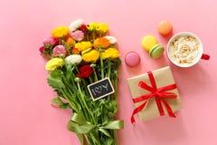Świąteczny ranku pojęcia jaskier kwitnie bukiet, prezenta pudełko, filiżanka cappuccino i makarons zasychają na różowym tle Fotografia Stock