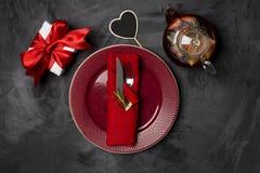 Świąteczny stołowy położenie dla walentynka dnia z rozwidleniem, nożem i serce szpilką z rozmarynami przy talerzami na czarnym st zdjęcia stock