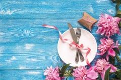 Świąteczny stołowy położenie z cutlery, peoniami i prezenta pudełkiem na błękitnym, Obrazy Stock