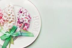 Świąteczny stołowy położenie z kwiatami, talerzem i faborkiem na lekkim pastelowym drewnianym tle wiosny, odgórny widok Zdjęcia Royalty Free