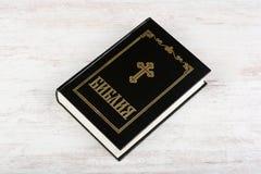 Święta biblia na białym drewnianym tle Religii wiara i pojęcie Cyrillic tekst znaczy biblię wewnątrz obraz royalty free