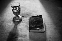 Święta biblia z czerwonym winem strzelającym w czarny i biały obrazy stock