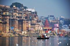 Święta Ganges rzeka przy Varanasi z wioślarską łodzią i seagulls Fotografia Stock