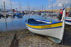 Świętego Tropez Drewniana łódź z jasnym wodnym odbiciem i ściana z cegieł to prowadzi latarnia morska obrazy royalty free