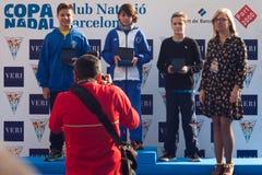 ŚWIĘTO BOŻĘGO NARODZENIA schronienia pływanie 2015, BARCELONA, Portowy Vell - 25th Grudzień: zwycięzcy konkurs z trofeami Zdjęcie Stock