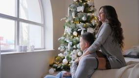 Świętowanie atmosfera, dziewczyny obsiadanie na leżance ściska jej przyglądający nadokiennego i chłopaka out choinka blisko zbiory wideo