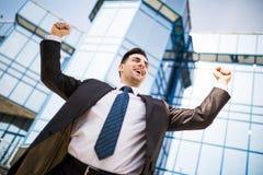 świętowaniu sukcesu Z podnieceniem młody biznesmen utrzymuje ręki podnosić i wyraża pozytyw podczas gdy stojący outdoors z biurow Fotografia Stock