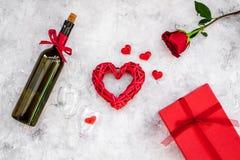 Świętuje valentine ` s dzień Wino, szkła, czerwieni róża, serce znak, prezenta pudełko na popielatego tła odgórnym widoku Zdjęcie Stock