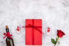 Świętuje valentine ` s dzień Wino, szkła, czerwieni róża, serce znak, prezenta pudełko na popielatej tło odgórnego widoku kopii p Obraz Stock