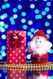 Święty Mikołaj bawi się, prezent w pakunku i złoci koraliki na szkło stole z pięknym błękitnym bokeh Obrazy Stock