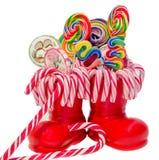 Święty Mikołaj czerwień inicjuje, buty z barwionymi słodkimi lizakami, candys Świętego Nicholas but z teraźniejszość prezentami Obrazy Stock
