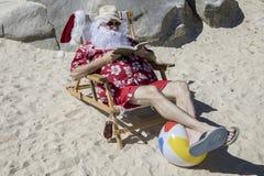 Święty Mikołaj czytelnicza powieść na pogodnej plaży Obrazy Royalty Free