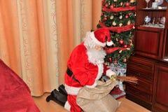 Święty Mikołaj daje prezentom drzewo na Bożenarodzeniowym czasie zdjęcie stock