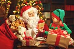 Święty Mikołaj i elfa dziecko w Bożenarodzeniowym działaniu, czytelniczy lett Zdjęcie Stock