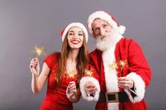 Święty Mikołaj I Młody Mrs Claus pozycja Z Sparklers Na Szarym tle zdjęcia stock