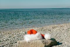 Święty Mikołaj kapelusz kłama na wielkim kamieniu na seashore Santa pójść pływać fotografia stock