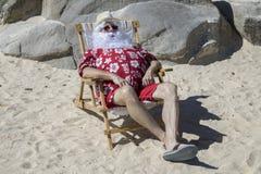 Święty Mikołaj na pogodnej plaży w krześle Fotografia Royalty Free