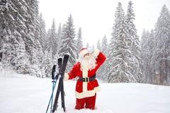 Święty Mikołaj narciarka z nartami w drewnach w zimie przy bożymi narodzeniami Obrazy Royalty Free