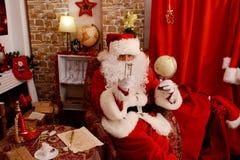 Święty Mikołaj narządzanie dla podróży i patrzeć światową mapę obrazy royalty free
