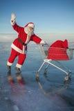 Święty Mikołaj niesie wózek na zakupy z prezentami w worku obrazy royalty free