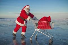 Święty Mikołaj niesie wózek na zakupy z prezentami w worku fotografia royalty free