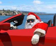 Święty Mikołaj obsiadanie w jego czerwień sportów samochodzie przy plażą zdjęcia royalty free