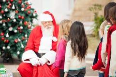 Święty Mikołaj Patrzeje dzieci Stoi W A Fotografia Royalty Free